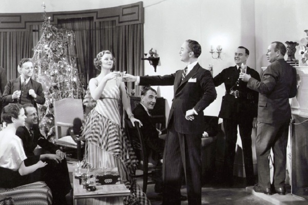 A production photo of William Powell and Myrna Loy hosting a Christmas Eve party as Nick and Nora Charles.