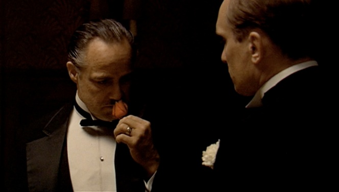 Stuff like Febreeze wasn't around in the 1940s, so men like Don Corleone would sniff the flower in their lapel if someone else in the room started cutting muffins.