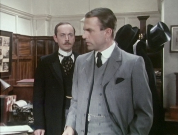 Even the young-ish Fothergill, standing behind Reilly/Rosenblum, looks like part of an older generation in his frock coat, standing collar, and cravat.