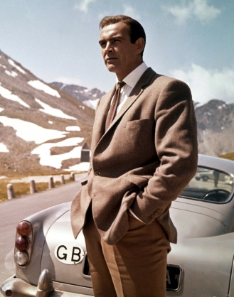 Sean Connery as James Bond stands behind his Aston Martin DB5 while ...