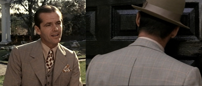 The suit appears grayish in certain lights but it is definitely brown in keeping with Gittes' earthtone motif for the day.