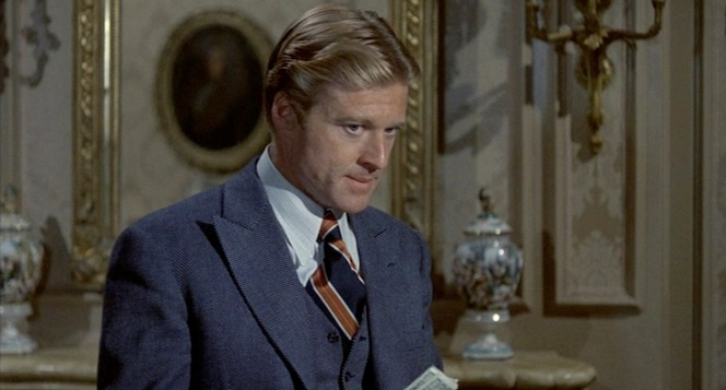 Redford looks awfully miffed for a guy who was just handed a thousand dollars.