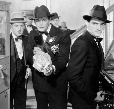 Paul Muni (center) aims a Thompson submachine gun as Tony Camonte in Scarface (1932).