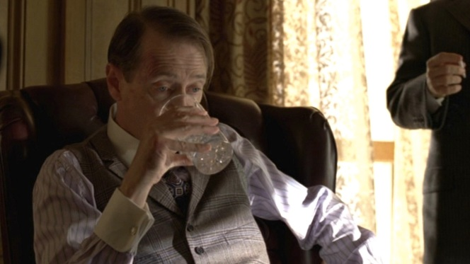 One of Nucky's suspender straps peeks out from the left armhole of his waistcoat.