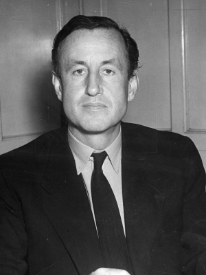 Ian Fleming in a dark suit and knitted necktie, a rare sight given his preference for bow ties later in life.