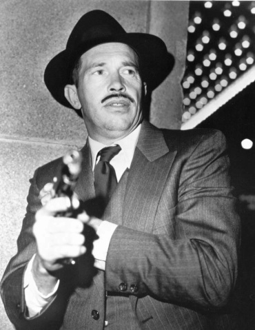 Oates as Dillinger, drawing his pistol.
