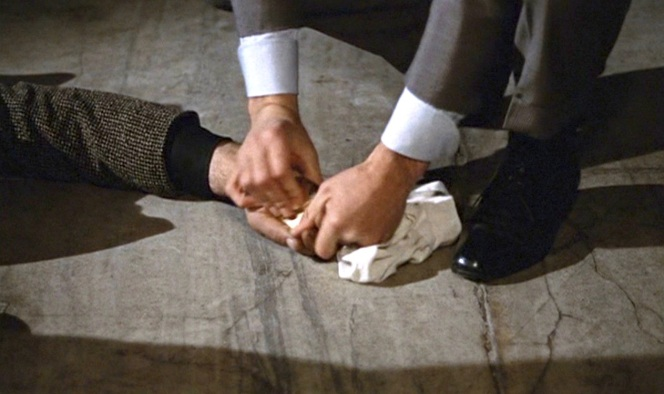 Bond takes some evidence from a very dead fellow spy.