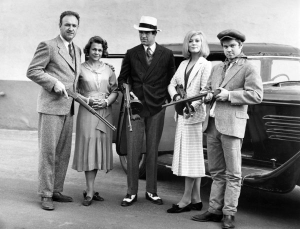 The cast of 1967's Bonnie and Clyde: Gene Hackman, Estelle Parsons, Warren Beatty, Faye Dunaway, and Michael J. Pollard. All are dressed from the bank robbery scene featured here, but Clyde has inexplicably replaced his herringbone suit coat with the dark blue double-breasted pinstripe coat from his other suit.