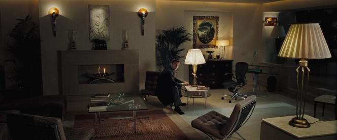 M's rad London flat. Bond is sitting on one of the Knoll Barcelona chairs while his previously-occupied Herman office chair sits off to his left. The book is on the table in front of him.