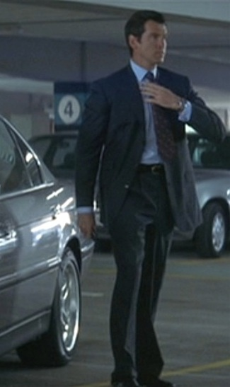 Pierce Brosnan as James Bond in Tomorrow Never Dies (1997) next to his BMW 750iL sedan.