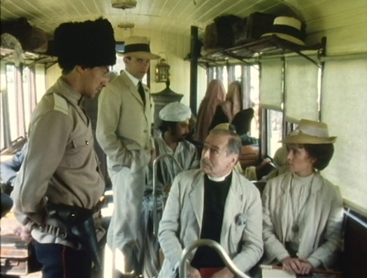 Reilly stands amongst the train's other passengers. Note that all appear to be dressed for July rather than December.