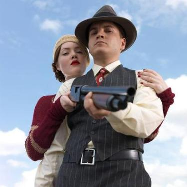 A promotional photo of Bonnie and Clyde, threatening their potential audience with a 12-gauge.