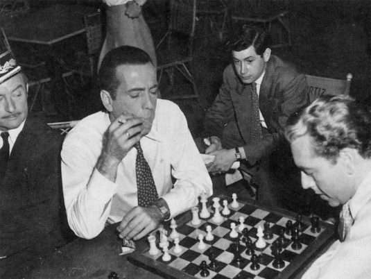 Director Michael Curtiz and co-star Claude Rains watch Bogie take on co-star Paul Heinreid at chess.