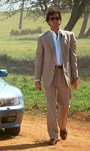 Pierce Brosnan as James Bond in GoldenEye (1995), standing next to his newly-issued BMW Z3.