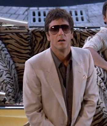 Al Pacino stands next to a bright '63 Caddy convertible as Tony Montana in Scarface (1983).