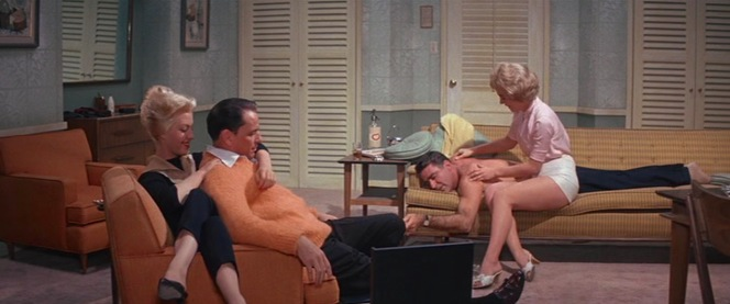 Compared to Ol' Blue Eyes, Peter Lawford dresses much less modestly for his massage in just the trousers of his charcoal suit.