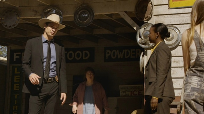 "Raylan sports a black suit, solid blue shirt, and black subtly-patterned tie for his investigation in Harlan County in ""The Moonshine War"" (Episode 2.01)."
