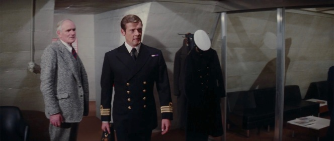 After a short debrief with Q, a uniformed Commander Bond approaches his superior officers.