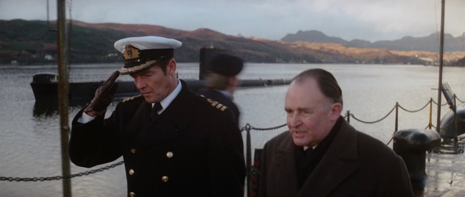 Bond walks the deck with British Minister of Defence Frederick Gray (Geoffrey Keen), dressed in greatcoat, cap, and gloves to combat the chill.