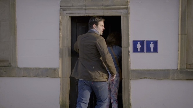 Rob wears his British jacket and American jeans before a tryst in the loo.