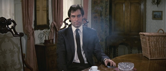 Bond sits in a cloud of smoke as Koskov debriefs the British intelligence chiefs.