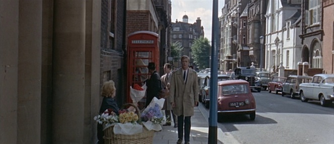 Michael Caine walks down the street between a red phone booth and a Mini Cooper. Quite possibly one of the most British iamges ever.