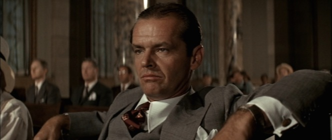 Gittes affects a reasonably smug smirk while overseeing government inaction in action during a local town hall meeting.