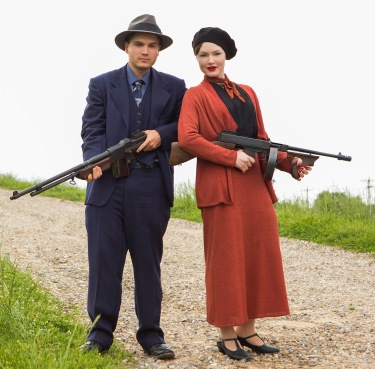 Emile Hirsch and Holliday Grainger wielding a BAR and a Tommy gun as Clyde Barrow and Bonnie Parker in Bonnie and Clyde (2013).