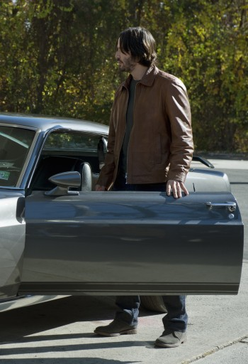 Keanu Reeves as John Wick, standing inside the door of his 1969 Ford Mustang Mach 1 in John Wick (2014).