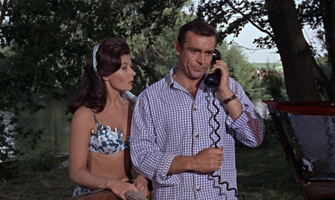 Bond gets a mouthful from Miss Moneypenny over the car phone. Lois Maxwell had originally been offered the part of Sylvia Trench but turned it down, feeling more comfortable in the role of Moneypenny.