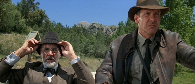 Sean Connery wears a tweed three-piece suit, checked trilby, bow tie, and glasses that all contribute to subliminally aging the 59-year-old actor to have the appearance of an older man. However, it is worth noting that Indy seems to have taken some style cues from dear old dad with the tweedy suits and bow ties that he wears while teaching at Marshall College.