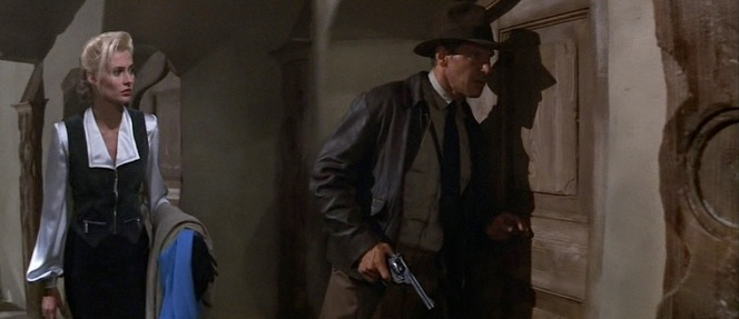 "Dr. Elsa Schneider (Alison Doody) stands behind Indy as he draws his Webley ""WG"" Army revolver in Indiana Jones and the Last Crusade."