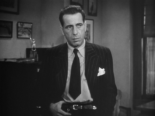 The light shirt, dark short tie, and Western-style slim leather belt appear to have been preferred by Bogart in real life as well.