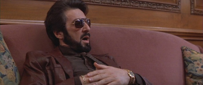 Gold drips from Carlito's face and fingers while he talks to his attorney.