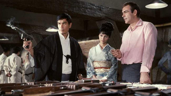 A production still of Tiger Tanaka showing Bond the capabilities of the MBA Gyrojet pistol.