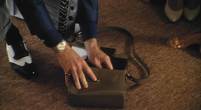 Jack bends down to put Bobby's Regalias cigarettes back in her purse, flashing his gold jewelry as he does.
