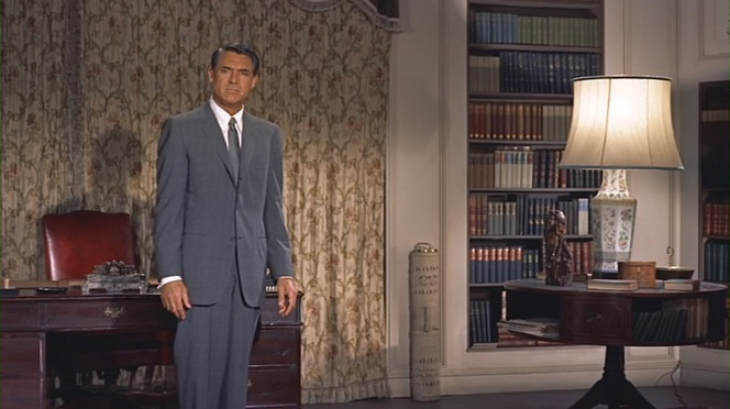 Cary Grant suited up as Roger Thornhill, dressed to the nines at the moment he meets Philip Vandamm and his henchman Leonard.