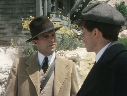 Reilly's corduroy suit and fedora contrast against the more working-class flat cap and pea coat sported by his business partner Greenburg.