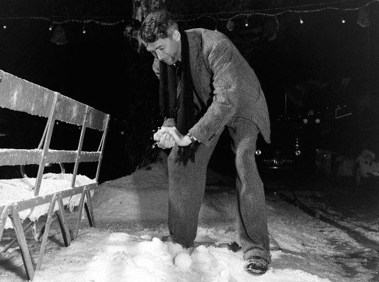 "Jimmy Stewart playing with the ""chemical snow"" behind-the-scenes of It's a Wonderful Life, captured by Life photographer Martha Holmes who visited the Encino set in the summer 1946."