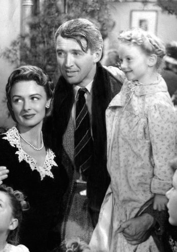 James Stewart (as George Bailey) with Donna Reed (as Mary Bailey) and Karolyn Grimes (as Zuzu) in It's a Wonderful Life (1946)