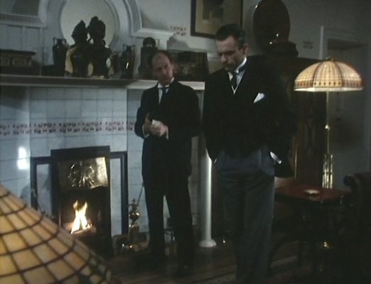 At first glance, Reilly and his butler appear to be dressed identically with black coats, wing collars, and dark ties, but the details - and contrasting gray trousers - of Reilly's outfit set him apart.