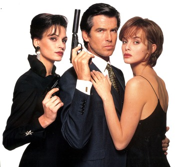 Pierce Brosnan wearing the navy birdseye Brioni three-piece suit, flanked by co-stars Famke Janssen and Izabella Scorupco. Note the addition of the waistcoat and gold cufflinks, neither of which showed up on screen.