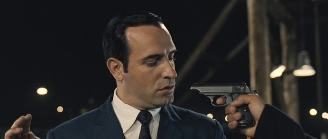 Like all the best bumbling spies, OSS 117 finds himself at the point of his own gun by the end of the story.