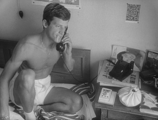 An undies-clad Michel smokes one of his own Gitanes cigarettes, eschewing Patricia's Chesterfield King Size cigarettes on the bedside table.