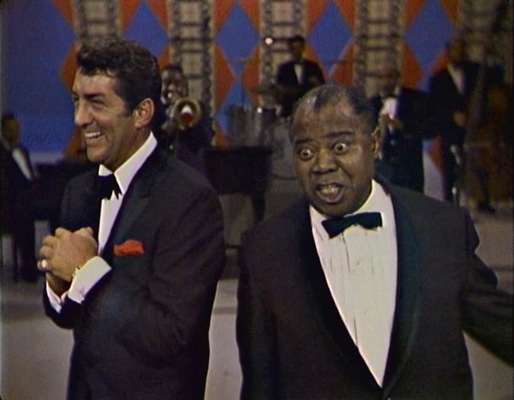 Dean Martin wears a gold watch while enjoying a duet with Louis Armstrong, circa 1965 (link).