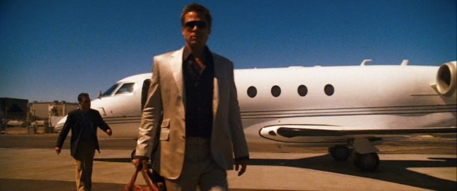 Rusty struts off the plane, immune to the blinding qualities of his suit in the sunlight thanks to his protective shades.
