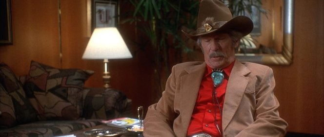 "Surprisingly, Webb wears a cowboy hat while indoors in each of his appearances – an oddity for a man who uses phrases like ""little lady""– and who would normally remove his hat upon entering a building."