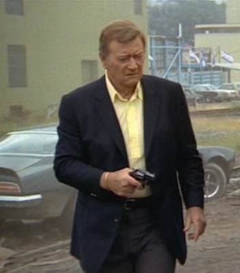 "John Wayne as Det. Lon ""McQ"" McHugh in McQ (1973), armed in front of his 1973 Pontiac Firebird Trans Am."