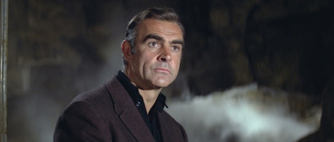 The mixed brown and black fabric gives the jacket a dark muted brown effect that both flatters Connery and coordinates nicely to his black shirt and trousers.
