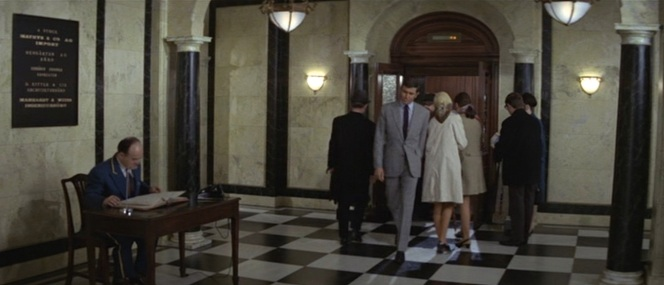 Bond eases his way past a bunch of office drones filing into the elevator for lunch.